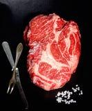Rohes Steak marmorte Rindfleisch, Weinlesegabel und Messer auf schwarzem Hintergrund Lizenzfreie Stockbilder