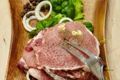Rohes Steak mit einem Salat und einem Gewürz Stockfoto