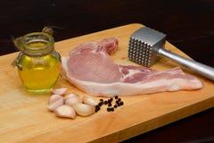 Rohes Steak mit Fleischhammer und -bestandteil auf hölzernem Brett Lizenzfreie Stockbilder