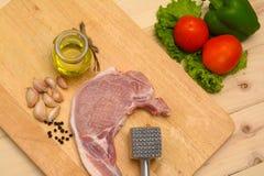 Rohes Steak mit Fleischhammer und -bestandteil auf hölzernem Brett Stockbilder