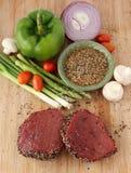 Rohes Steak mit Gewürzen und Gemüse Stockfotos