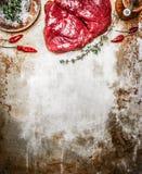 Rohes Steak mit Kräutern und Gewürzen auf rustikalem Metallhintergrund, Draufsicht Lizenzfreies Stockbild