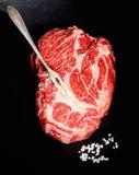 Rohes Steak vom Marmorrindfleisch, Salz, Weinlesefleischgabel auf einem schwarzen Hintergrund Stockbild
