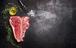 Rohes T-Bone-Steak mit frischen Kräutern und Öl auf dunklem Rost asphaltieren Hintergrund, Draufsicht stockbild