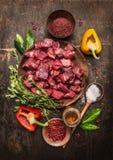 Rohes ungekochtes Fleisch geschnitten in den Würfeln mit frischen Kräutern, Gemüse und Gewürzen auf rustikalem hölzernem Hintergr Stockfotos
