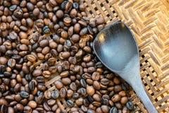 Rohkaffeebohnen in der Bambuswanne mit hölzernem Löffel Lizenzfreie Stockfotos