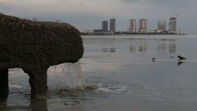 Rohr Abwasserkanalwasser vom Kanalisationssystem direkt nahe Meer in der Stadt mit Wolkenkratzern stock video