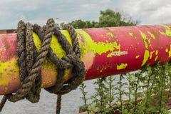 Rohr mit einem Knoten des rauen Seils Lizenzfreie Stockbilder