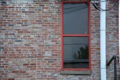 Rohr neben rotem Fenster stockbild