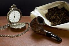 Rohr, Tabak und die alte Borduhr. Stockfotos