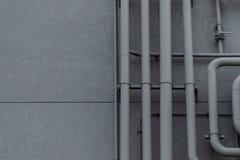 Rohrleitungssystem auf grauer Wand Stockbild