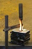 Klammer, die auf brennenden Stapel Festplattenlaufwerke drückt stockfotografie