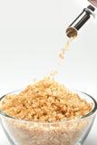 Rohrzucker, der von einem Zuckerbassin fällt Stockbild