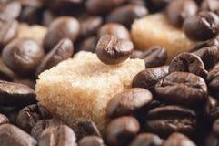 Rohrzuckerwürfel bedeckt durch Röstkaffeebohnen Lizenzfreie Stockfotos