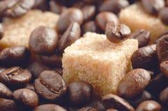 Rohrzuckerwürfel bedeckt durch Röstkaffeebohnen Lizenzfreies Stockfoto