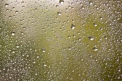 Rohwassertropfen auf Fensterglas Stockbilder