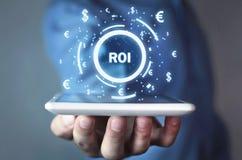 ROI -的回收投资 到达天空的企业概念金黄回归键所有权 库存图片