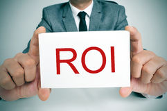 ROI, acronym for Rate of Interest or Return on Investment. Businessman sitting in a desk showing a signboard with the text ROI, ROI, acronym for Rate of Interest stock image