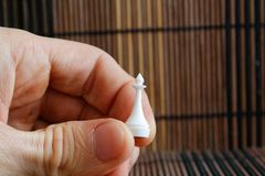Roi blanc d'échecs en plastique, dans la main du ` s de l'homme, fond en bois images libres de droits