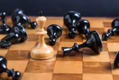 Roi blanc entouré par les pièces d'échecs noires Image stock