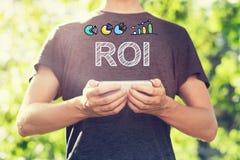 ROI-Konzept mit dem jungen Mann, der seinen Smartphone hält Stockbild