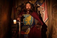 Roi médiéval sur le trône dans l'intérieur antique de château Photos libres de droits
