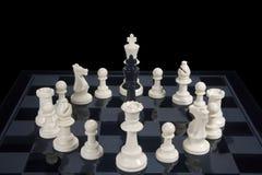 Roi noir d'échecs cerclé par les morceaux blancs images stock