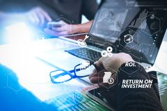 Two colleagues website designer discussing data and digital tabl. ROI Return on Investment indicator in virtual dashboard for improving business. two colleagues Stock Photo