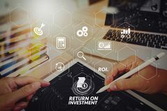 Website designer working digital tablet and computer laptop with. ROI Return on Investment indicator in virtual dashboard for improving business. Website Stock Images