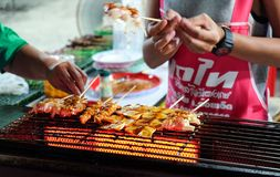 Roiet, Thailand - 20 Feb, 2018 : An unidentified woman grilled BBQ in Chinese Ma La style at Boon Koon Lan Temple fair in. Kasetwisai town, Roiet, Thailand stock photography