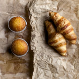 Сroissants, muffins on brown. Paper background for breakfast and lunch Royalty Free Stock Photo