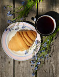 Сroissants on old wooden table. Croissants and tea on old wooden table Stock Photos