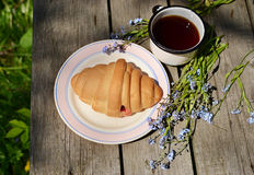 Сroissants on old wooden table. Croissants and tea on old wooden table Stock Photo