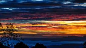 Rojizo y oscuridad se nubló puesta del sol sobre el golfo de Nicoya Foto de archivo libre de regalías