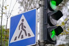 Rojo, amarillo, verde el color verde y el paso de peatones firman en una ciudad foto de archivo