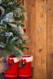 Rojo con la bota blanca de la Navidad de la frontera debajo del árbol de navidad en fondo de madera con las estrellas Foto de archivo libre de regalías