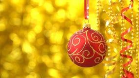 Rojo de la Navidad con el balanceo de oro de la bola del modelo Decoración del Año Nuevo Bokeh de oro borroso que brilla tenuemen metrajes