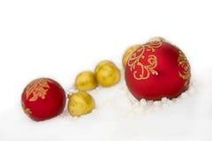 Rojo de la Navidad y bola del oro, gotas en nieve Fotografía de archivo