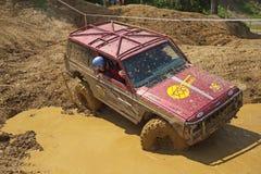 Rojo del coche del camino que pasa en charcos fangosos Foto de archivo libre de regalías