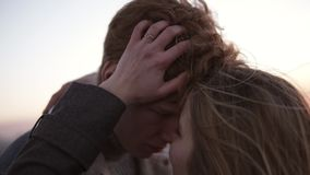 Rojo dirigido, hombre joven rizado y su girldriend de pelo largo que abrazan mientras que se coloca en el tejado Caricia, dulzura almacen de metraje de vídeo