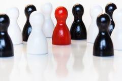 Rojo en un grupo de estatuillas blancos y negros del juguete Fotografía de archivo