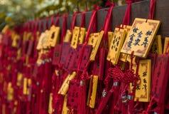 Rojo tradicional que desea sobres con deseo manuscrito Ejecución roja de la placa de la tarjeta de felicitación en desear el árbo Foto de archivo libre de regalías