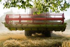 Rojo verde que trabaja cosechando la cosechadora en un campo del trigo debajo de a Imagenes de archivo