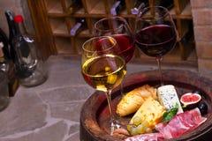 Rojo, vidrios color de rosa y blancos y botellas de vino Queso, higo, uva, prosciutto y pan en barril de madera viejo Imagen de archivo