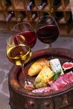 Rojo, vidrios color de rosa y blancos y botellas de vino Queso, higo, uva, prosciutto y pan en barril de madera viejo Imagenes de archivo