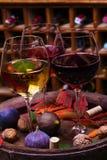 Rojo, vidrios color de rosa y blancos y botellas de vino Uva, higo, nueces y hojas en barril de madera viejo Imagen de archivo