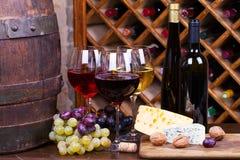 Rojo, vidrios color de rosa y blancos y botellas de vino Uva, nueces, queso y barril de madera viejo Fotos de archivo