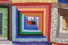 Rojo y azul del cuadrado del edredón de la cabaña de madera Imágenes de archivo libres de regalías