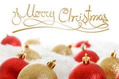 Rojo y bolas en las nieves acumulada por la ventisca, onwhite aislado de la Navidad del oro Fotografía de archivo