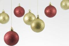 Rojo y decoraciones de la Navidad de la ejecución del oro en el fondo blanco Fotos de archivo libres de regalías